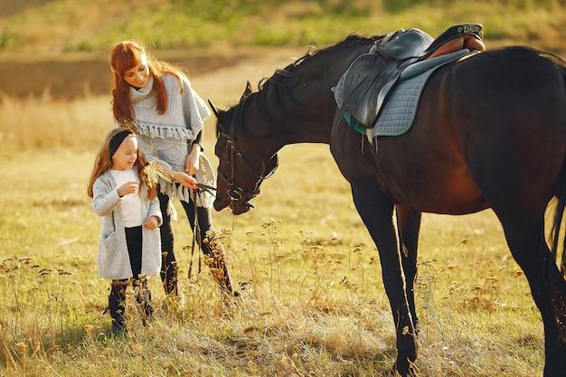 Madre e hija en un campo jugando con un caballo
