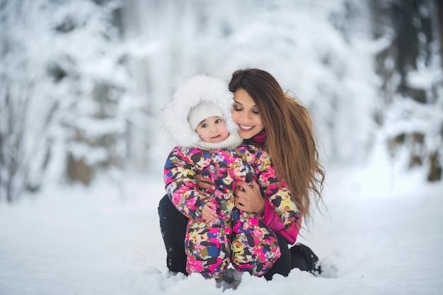 Madre e hija en chaquetas de invierno rosa caminando en el bosque de invierno entre la nieve
