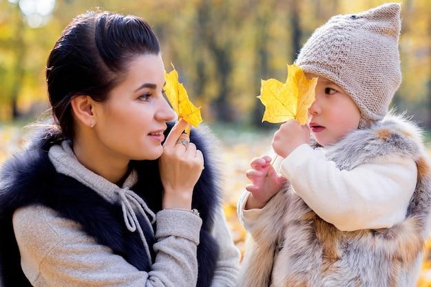 Madre e hija cierran los ojos con hojas de otoño
