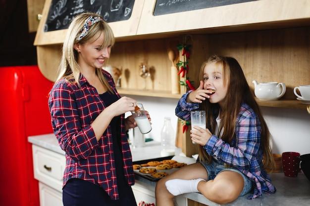 Madre e hija en una cocina prueban galletas de chocolate recién horneadas con leche