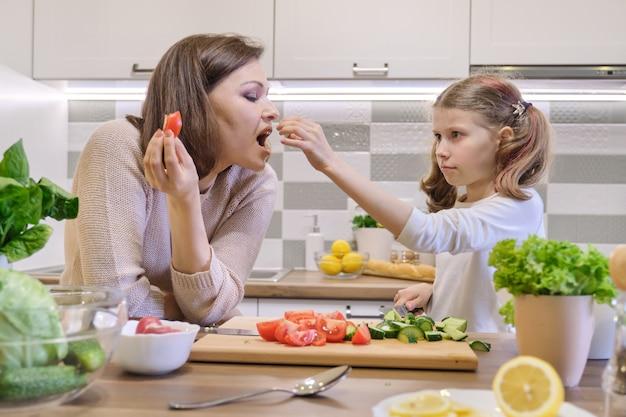 Madre e hija cocinando juntas en cocina ensalada de verduras