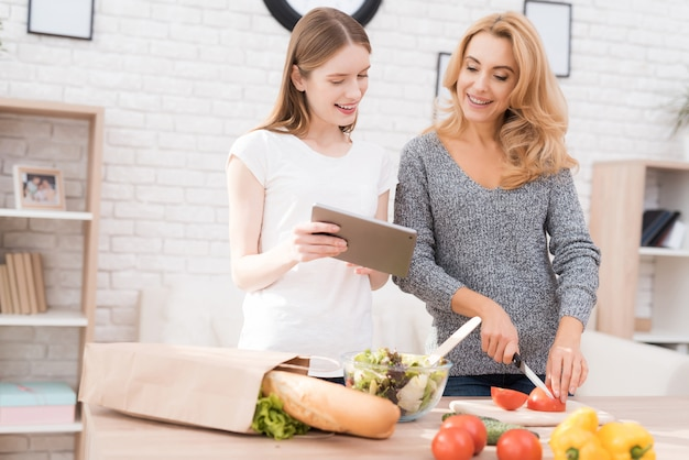 Madre e hija cocinando juntos en la cocina.