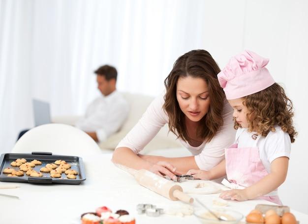 Madre e hija cocinando mientras papá se relaja en el sofá