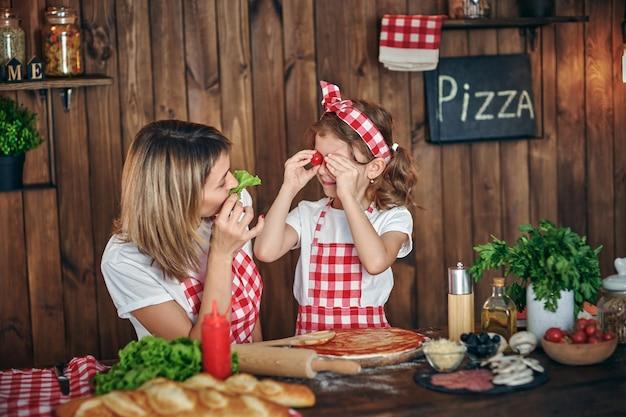 Madre e hija cocinando pizza y diviértete