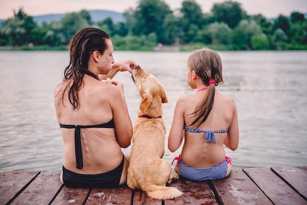 Madre e hija comiendo bocadillos junto al agua