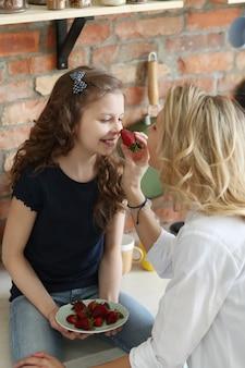 Madre e hija comiendo fresas en la cocina