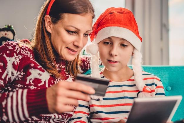 Madre e hija comprando en línea en casa durante la navidad