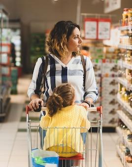 Madre e hija de compras para comestibles en supermercado