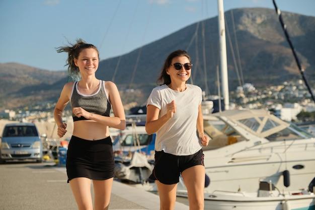 Madre e hija corriendo corriendo juntos en el paseo marítimo