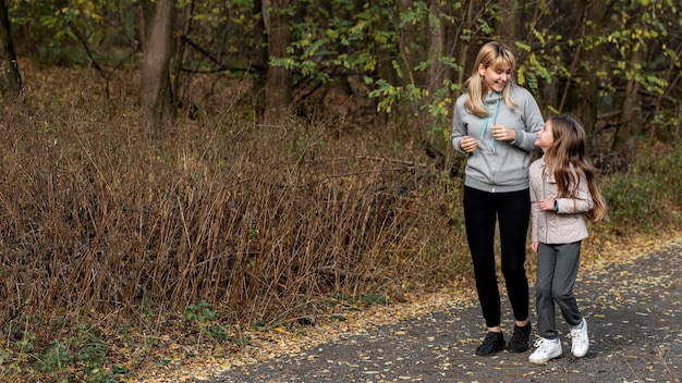 Madre e hija corriendo en la naturaleza