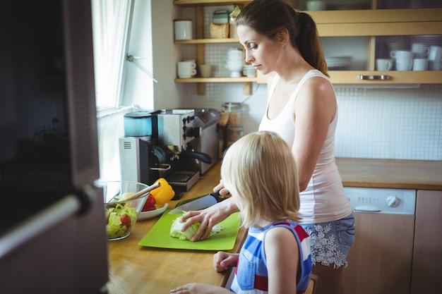 Madre e hija cortando vegetales en la cocina