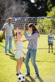 Madre e hija dando cinco jugando al fútbol en el parque