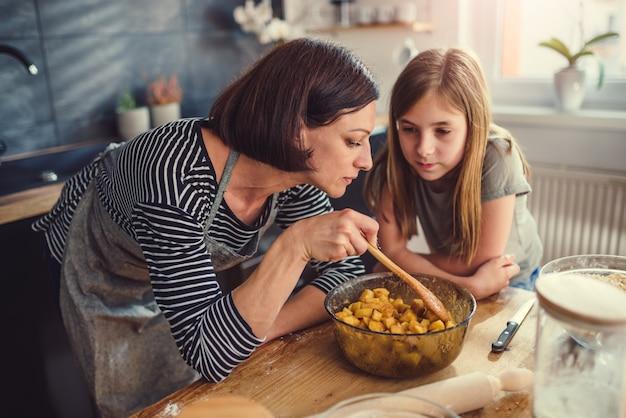 Madre e hija degustación de relleno de tarta de manzana