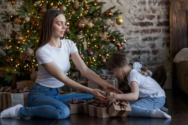 Madre e hija delante del árbol de navidad, abriendo regalos