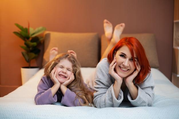 Madre e hija descansando en la cama en su casa