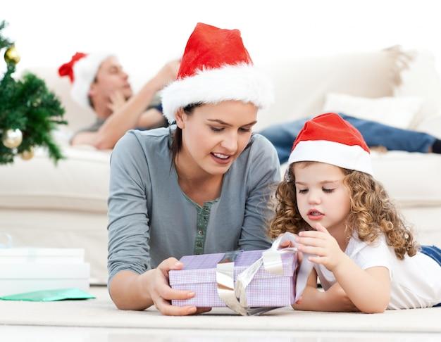 Madre e hija desenvolver un regalo tirado en el piso