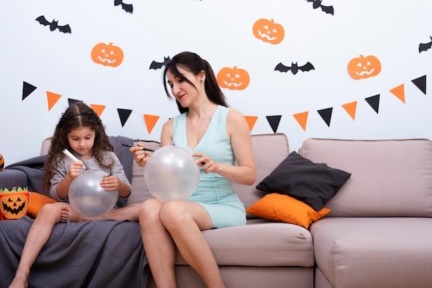 Madre e hija dibujando en globos