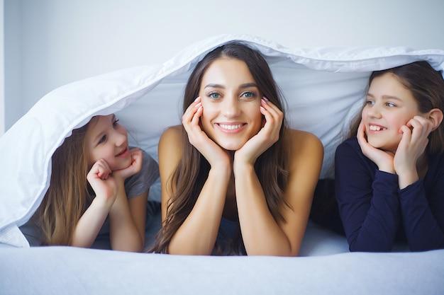 Madre e hija disfrutan en la cama en casa