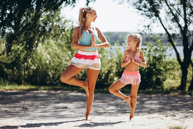 Madre e hija en la playa practicando yoga