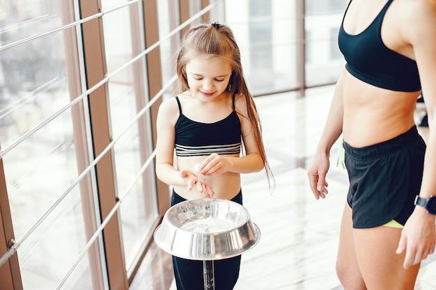 Madre e hija entrenando en un gimnasio