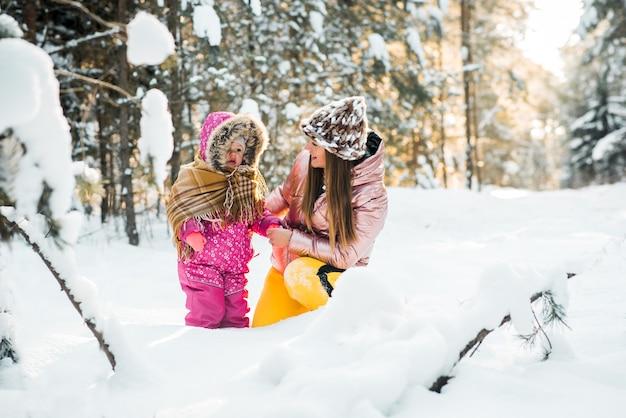 Madre e hija envueltas en una bufanda en un bosque nevado de invierno. viajes y recreación