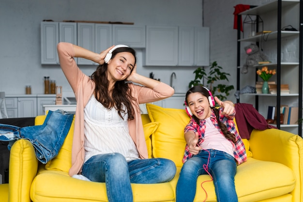 Madre e hija escuchando música y divirtiéndose