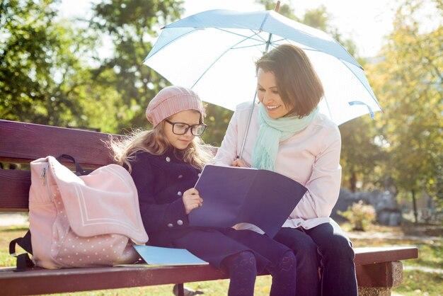 Madre e hija están descansando juntas en un banco en el parque de la ciudad