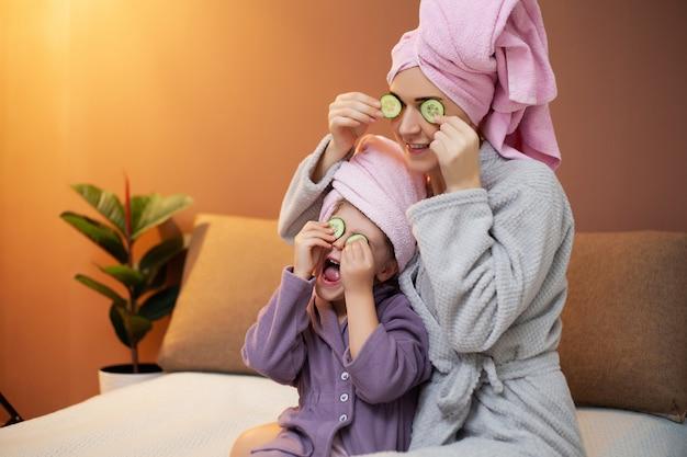 Madre e hija están haciendo tratamientos de spa en casa en la cama