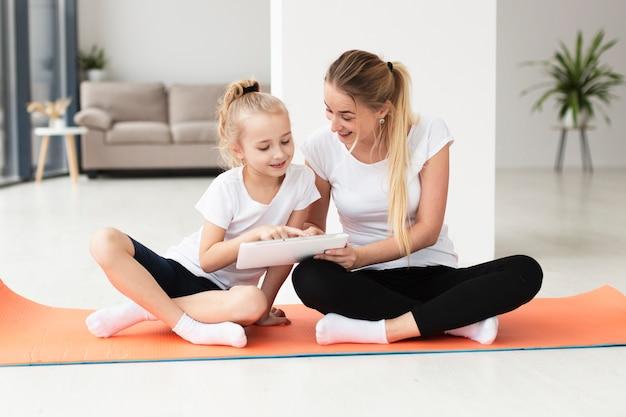 Madre e hija en estera de yoga en casa jugando en tableta