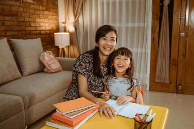 Madre e hija estudian en casa estudiando juntas