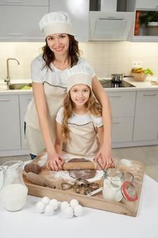 Madre e hija exprimir la masa con un rodillo.