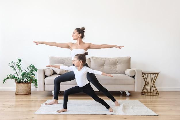 Madre e hija de familia feliz haciendo yoga en casa por la mañana