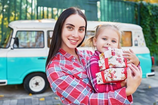 Madre e hija de familia con regalos en el parque con una furgoneta retro