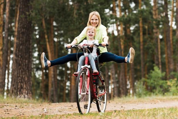 Madre e hija felices en bicicleta