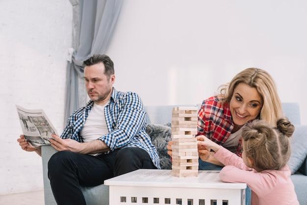 Madre e hija felices que juegan al juego de madera del bloque mientras que padre lee el periódico en casa
