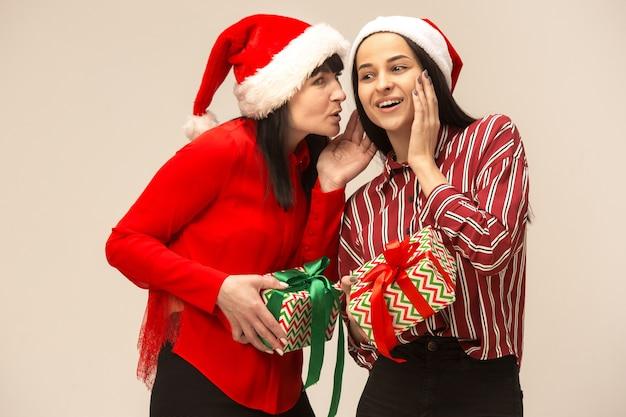 Madre e hija con gorro de papá noel y caja de regalo