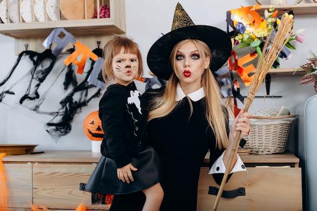 Madre e hija hacen cara aterradora de pie en disfraces y mujer sosteniendo una escoba