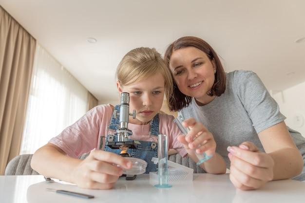 Madre e hija hacen experimentos químicos con microscopio en casa