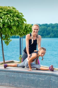 Madre e hija haciendo ejercicios de gimnasia sobre la hierba en el muelle del río