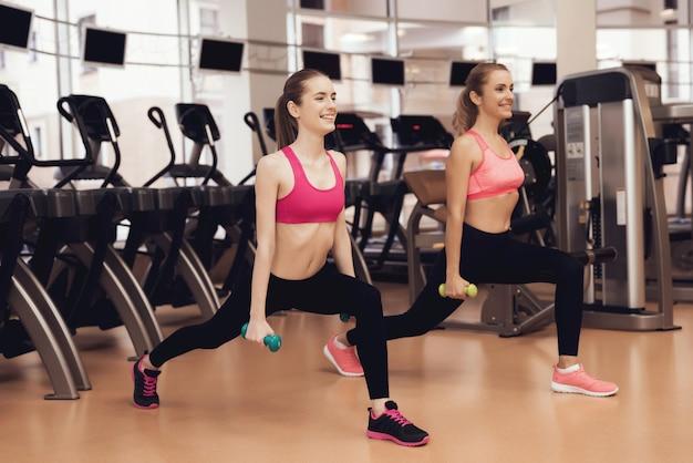 Madre e hija haciendo ejercicios con pesas.