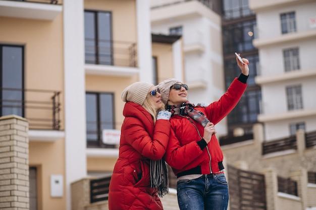 Madre e hija haciendo selfie afuera en invierno
