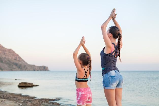 Madre e hija haciendo yoga en la naturaleza al aire libre al amanecer
