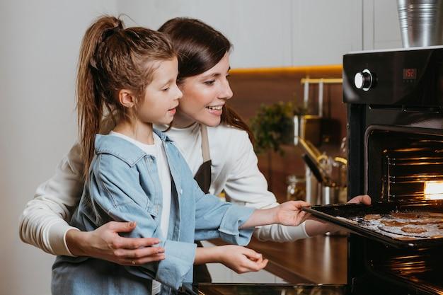 Madre e hija horneando galletas en casa juntos