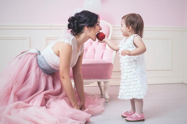 Madre e hija en interior rosa comiendo una manzana