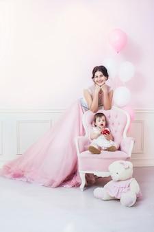 Madre e hija en interior rosa con silla vintage y globos con hermosos vestidos