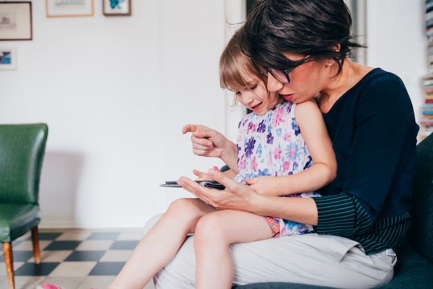 Madre e hija en interiores usando tableta