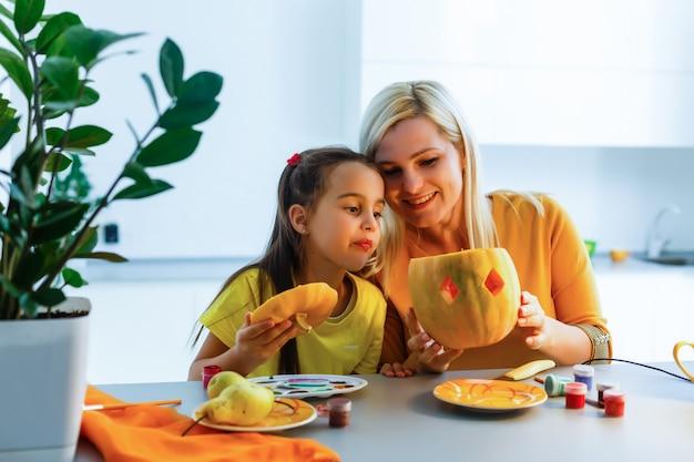 Madre e hija juegan con calabaza tallada en casa