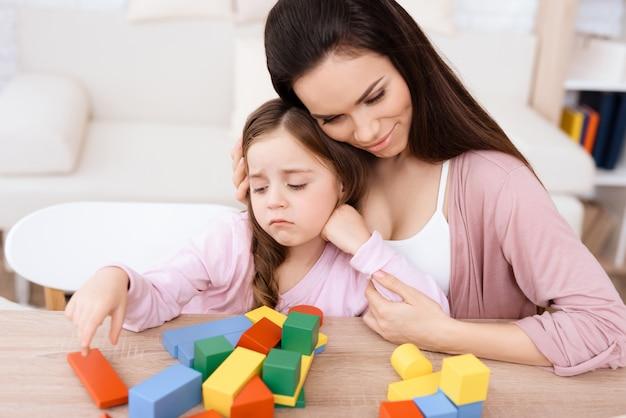 Madre e hija juegan con cubos de madera.