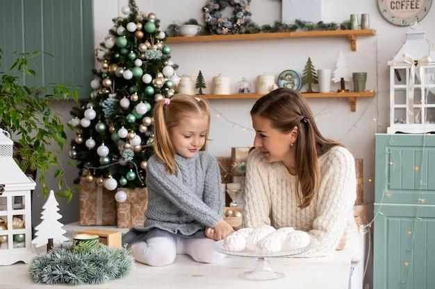 Madre e hija jugando en la cocina en casa de navidad.