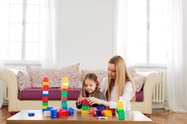 Madre e hija jugando en la habitación.